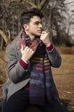 Homem à moda novo que guarda o lenço morno na floresta Fotografia de Stock Royalty Free