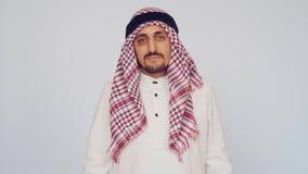 Homem árabe adulto no vestido nacional em um fundo branco Homem de negócios saudita descontentado vídeos de arquivo