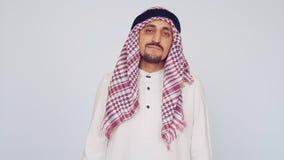 Homem árabe adulto no vestido nacional em um fundo branco Homem de negócios saudita descontentado filme