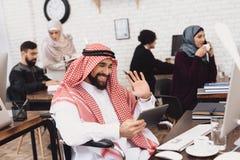 Homem árabe deficiente na cadeira de rodas que trabalha no escritório O homem está falando na tabuleta fotografia de stock