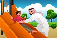 Homem árabe muçulmano com sua criança no campo de jogos Imagens de Stock