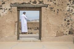 Homem árabe no equipamento omanense tradicional em um castelo velho imagens de stock royalty free