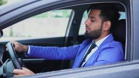 Homem árabe novo no terno formal que senta-se no carro Ele que olha expressively vídeos de arquivo