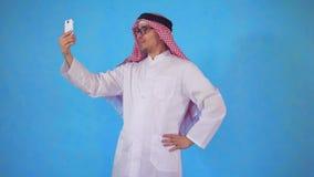 Homem árabe que fala no vídeo para chamar um smartphone em um fundo azul video estoque