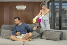 Homem árabe que joga um jogo de vídeo quando a mulher limpar em torno dele Fotos de Stock Royalty Free