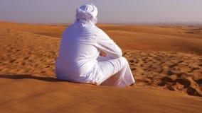 Homem árabe só no kandura branco que senta-se no deserto arenoso quente filme