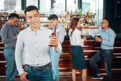 Homem étnico de sorriso com a garrafa da cerveja fotografia de stock