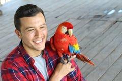 Homem étnico e seu papagaio domesticado foto de stock
