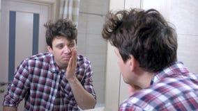 Homem acordado sonolento cansado com uma manutenção no banheiro, olhares no espelho e lavagem acima de sua cara filme
