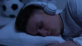 Homem adolescente nos fones de ouvido que dormem em casa, escutando o livro audio, estudando video estoque
