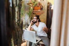 Homem adulto agradável que fala no telefone fotos de stock
