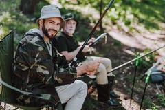 Homem adulto alegre que pesca com seu pai aposentado imagens de stock