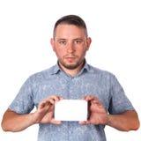 Homem adulto atrativo com restolho na camisa do verão em suas mãos que guardam uma folha branca com espaço para anunciar o texto  foto de stock royalty free