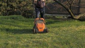 Homem adulto com lawnmower elétrico, sega do gramado Jardineiro que apara um jardim filme