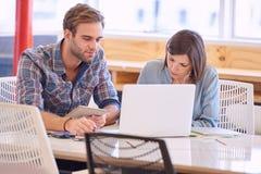 Homem adulto e mulher caucasianos que trabalham ao lado de se Fotografia de Stock Royalty Free