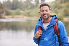 Homem adulto em um feriado de acampamento que está por um lago que sorri à câmera, retrato, distrito do lago, Reino Unido fotos de stock