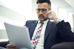 Homem adulto em um revestimento e nos vidros que corrigem erros ao falar com o autor no smartphone Fotos de Stock Royalty Free