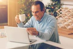 Homem adulto feliz que usa o portátil ao comer o café da manhã imagem de stock royalty free