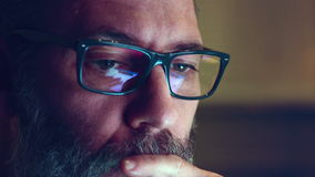 Homem adulto maduro com vidros que trabalha na noite Feche acima do tiro, reflexões vídeos de arquivo