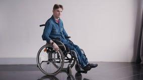 Homem adulto na cadeira de rodas que olha a câmera que senta-se em casa video estoque