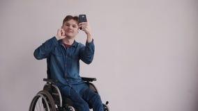 Homem adulto na cadeira de rodas usando o celular em casa video estoque