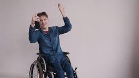 Homem adulto na cadeira de rodas usando o celular moderno em casa filme