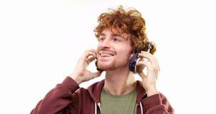 Homem adulto novo do ruivo do divertimento feliz bonito que escuta a música usando fones de ouvido e dança Ação da pessoa Vídeo d vídeos de arquivo
