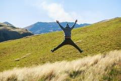 Homem adulto novo que salta no prado Fotos de Stock