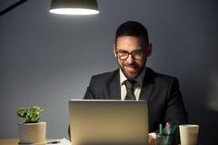 Homem adulto novo que trabalha no laptop tarde na noite fotos de stock