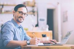 Homem adulto positivo que senta-se no café foto de stock royalty free
