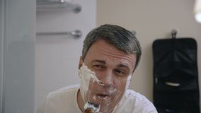 Homem adulto que barbeia no banheiro vídeos de arquivo