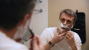 Homem adulto que barbeia no banheiro video estoque