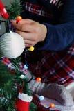 Homem adulto que decora a árvore de Natal em casa imagem de stock