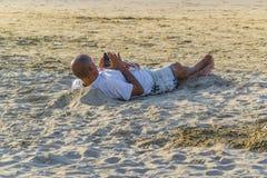 Homem adulto que descansa na areia fotos de stock