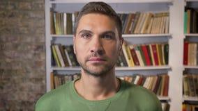 Homem adulto que olha para a frente calmamente e focalizado Bibliotecas no fundo vídeos de arquivo