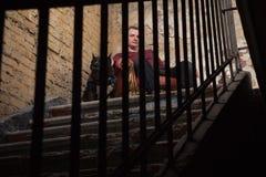 Homem adulto que satting em uma poltrona do vintage no fundo de uma parede descascada Em cada lado o homem que senta dois cães Pi Fotos de Stock Royalty Free