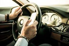 Homem adulto que texting ao conduzir fotografia de stock royalty free