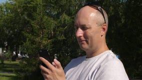 Homem adulto que usa o telefone celular para conversar nas redes sociais exteriores video estoque