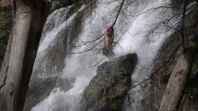 Homem adulto que veste o equipamento impermeável que desce uma cachoeira filme