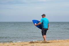 Homem adulto Skimboarding em Sunny Beach imagens de stock royalty free