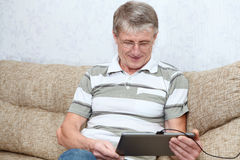 Homem adulto superior interessado com computador da tabuleta Fotos de Stock Royalty Free