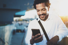 Homem africano americano de sorriso que usa o smartphone aos amigos da mensagem de texto na rua ensolarada Conceito de consideráv fotos de stock