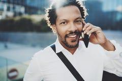 Homem africano americano feliz que usa o telefone celular para chamar seus amigos na cidade ensolarada Conceito de povos consider imagem de stock royalty free