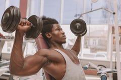 Homem africano atl?tico que d? certo com pesos no gym imagem de stock royalty free