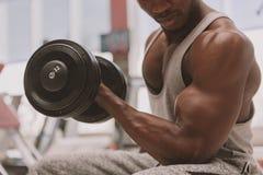 Homem africano atl?tico que d? certo com pesos no gym fotografia de stock royalty free