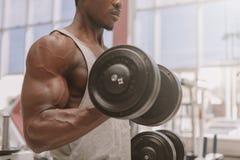 Homem africano atl?tico que d? certo com pesos no gym imagens de stock royalty free