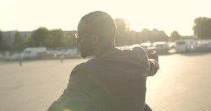 Homem africano atrativo seguro na roupa elegante e nos óculos de sol que giram o círculo, apontando na câmera com os dedos imagens de stock