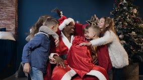 Homem africano bonito no traje de Papai Noel que senta-se na cadeira e que guarda o presente quando cinco crianças que correm e q vídeos de arquivo