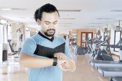 Homem africano com smartwatch no centro do gym Imagens de Stock Royalty Free