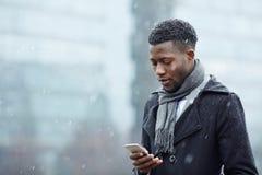 Homem africano considerável com Smartphone na neve foto de stock
